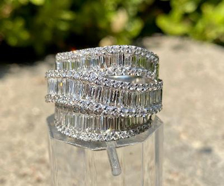 Very elegant and stunning, custom made 14 karat white gold, wide three row band ring features individual rows of sparkling white baguette cut diamonds invisibly set and separated by raised curving lines of prong set round brilliant diamonds creating