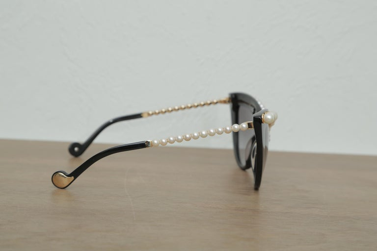 Stunning black oversize sunglasses trimmed in pearls. These sunglasses are very unique and have pearl trim rim and pearl trim sides.
