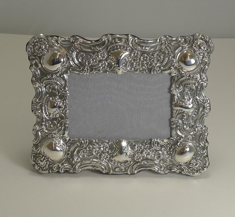 A beautiful English Edwardian photograph frame in sterling silver with exquisite repousse decoration fully hallmarked for Birmingham, 1902. The makers mark is also present for the silversmith, Samuel M Levi.  The backing is made from solid English