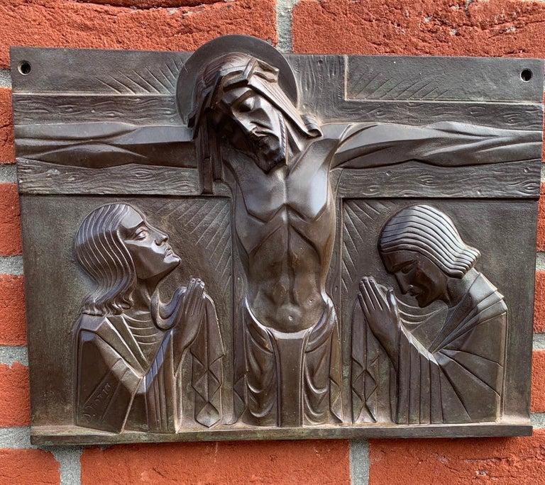 Perfectly stylized work of religious art by S. Norga.  This practical size and very good condition bronze plaque depicts Christ on the cross with Mary and Saint John mourning on either side. Sylvain Norga, known for his top quality religious art has