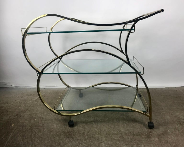 Stunning brass and glass modernist tea or bar cart, trolly seductive lines, streamline design, gleaming brass and 3 half inch glass with polished edges, makes a bold statement Show stopper! Hand delivery avail to New York City or anywhere en route