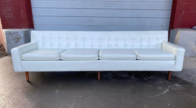 Stunning button tufted 4-seat sofa by Milo Baughman for Thayer Coggen. Classic Mid-Century Modern design, nice original condition, retains original white Naugahyde as well as original Thayer Coggen label, minor nik to back (see photo), hand delivery