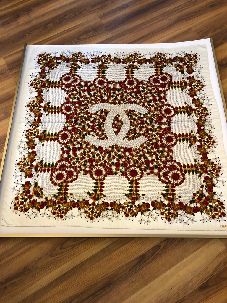 This silk scarf has a cream background with a multicolored precious stone design and a large