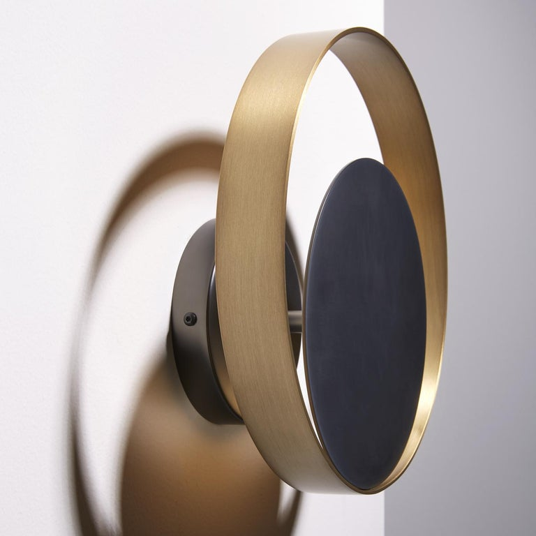 This sophisticated wall lamp projects an indirect light on the wall. It is comprised of a ring in natural brass surrounding a matte black nickel circle. This item is also available in other measures.