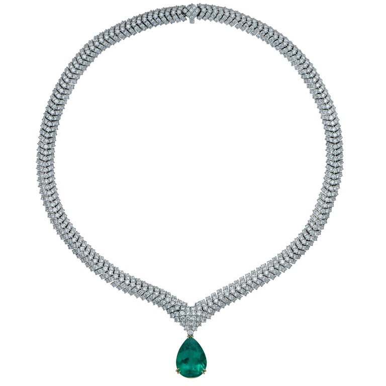 A magnificent 10.40ct rare Colombian Emerald, AGL certified, suspended from an elegant 18K white gold necklace containing 28.80cts of round brilliant cut diamonds F-G color and VS clarity. This vibrant emerald is removable making this breathtaking