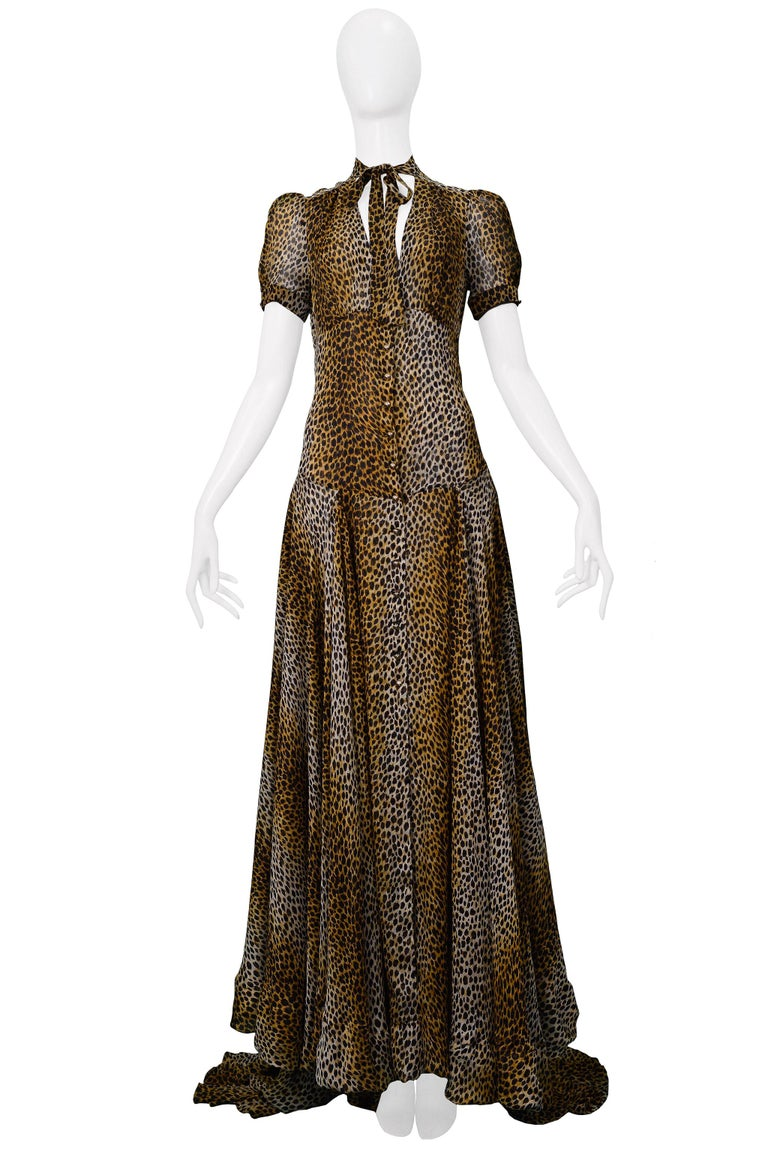 Resurrection is excited to offer a vintage Dolce & Gabbana D&G leopard print evening gown featuring a keyhole front, necktie, gold buttons, short sleeves, semi-sheer fabric, full-length skirt with a longer train panel in the back.   Dolce & Gabbana