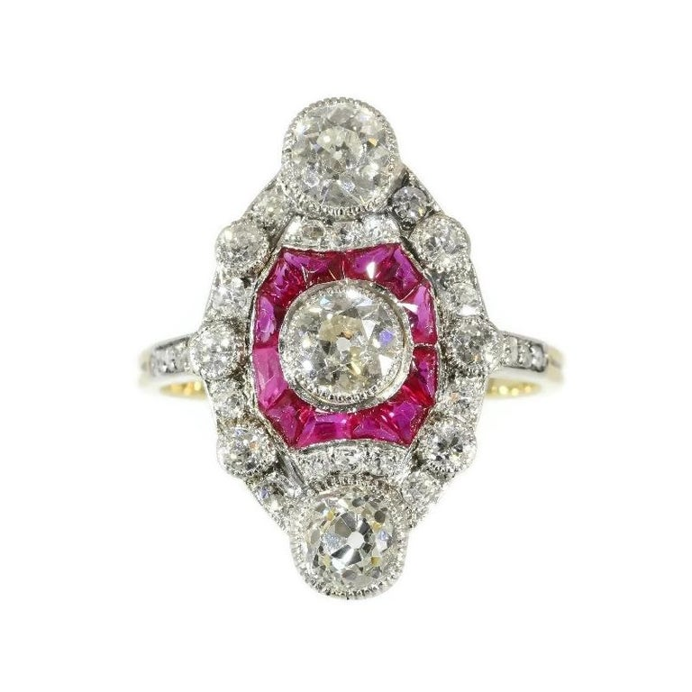 The design of this enchanting engagement ring in platinum and 18K yellow gold will prove you to be a jewel true to the Belle Epoque as well as the Edwardian style. A grand old brilliant cut diamond aligns from within a bulging square of 12 rubies