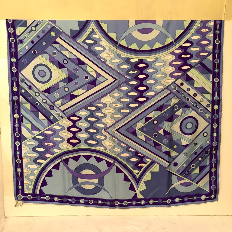 Emilio Pucci silk vintage scarf with geometric pattern and bold colors of blues, purples and greens. This would certainly be an eye-catching addition to any fashion ensemble. The colors of this scarf are a beautiful color combination. This scarf