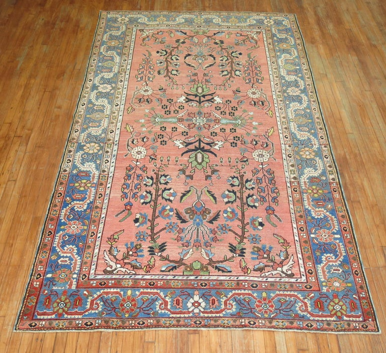 """20th century Persian Malayer rug featuring a paradise floral motif on a pink ground surrounded by a soft blue border, circa 1920.  Measures: 6'6"""" x 11'."""