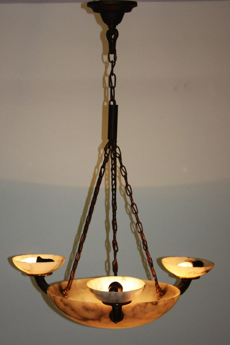 Stunning four-light alabaster and solid bronze pendant, circa 1900s. Large round shade with three bronze arms and brass frame (fine patination). Socket: Four x E27 (Edison) for standard bulbs. With original wiring.