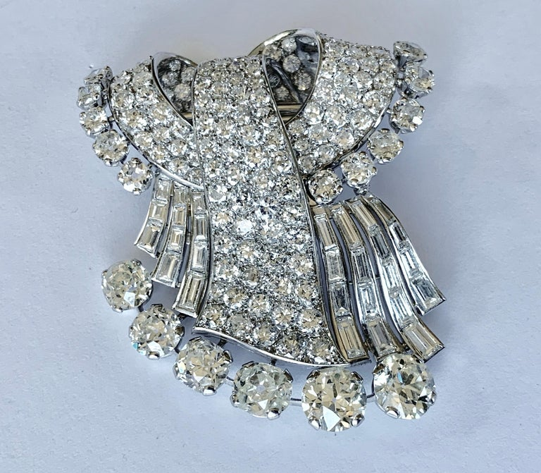 Exquisite Platinum und white gold brooch set with 6 old cut diamonds of approximately 9.00 ct, 28 Diamond baguettes of ca. 5.00 ct, 11 old european cut Diamonds of ca. 3.00 ct, and 129 pave set diamonds of ca. 10.00 ct.  Dimensions ca. 5,8 x 4,9 cm.