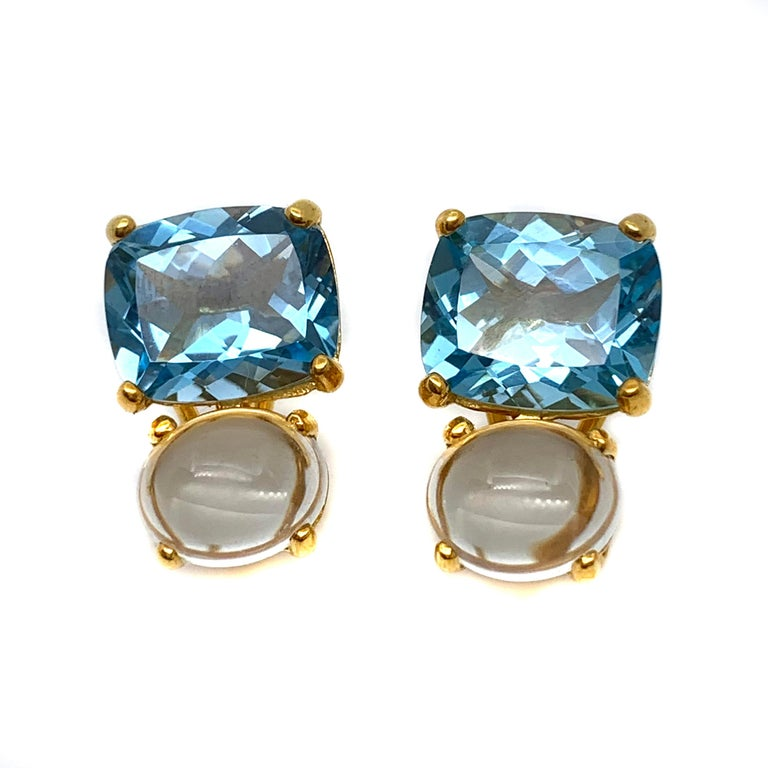 These stunning pair of earrings features a pair of genuine cushion-cut sky blue topaz with crystal clear cabochon-cut oval prasiolite, handset in 18k yellow gold vermeil over sterling silver. The facet and cabochon combination creates beautiful