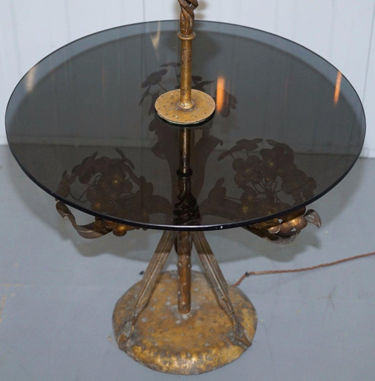 We are delighted to offer for sale this large gold leaf painted floral side table with smoked glass and built in lamp