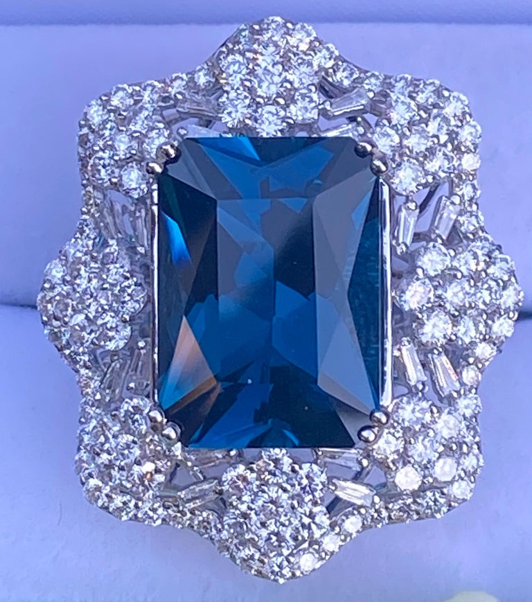 Stunning, very large, estate 18.17 carat deep London blue topaz is double talon prong set in 18 karat white gold and surrounded by approximately 162 round brilliant and baguette cut diamonds in a magnificent scalloping design mounting with a flower