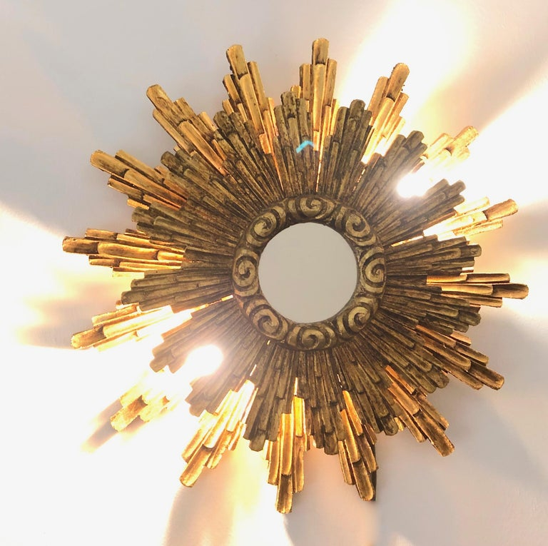 A stunning large starburst mirror, illuminated at the backside with two European E14 / 110 Volt candelabra bulbs, each bulb up to 40 watts. Made of gilded wood. Original as found condition (see all the detailed pictures). It measures approximate 23