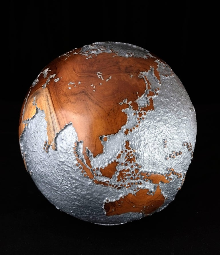 Petite in proportion, grandiose in style.  Stunning limited edition wooden globe made of hand-carved teak root with rough texture aluminium finishing. The smooth surface and natural patterns of the wood on the continent parts create a striking