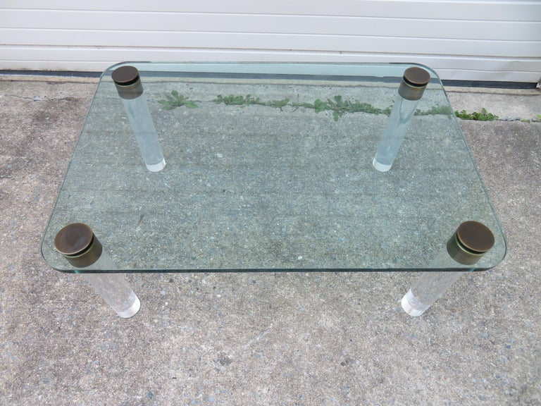 Stunning coffee table by Pace, circa 1975. Thick glass top with Lucite legs and bronze details. Looks like an exquisite piece jewelry for your living room!