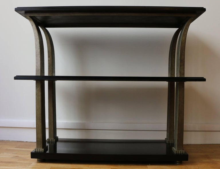 Console with three shelves/trays by Edgar Brandt (1880-1960). The shelves are made of black relacquered wood. The four squared legs are made of hammered metal in a palm shape.