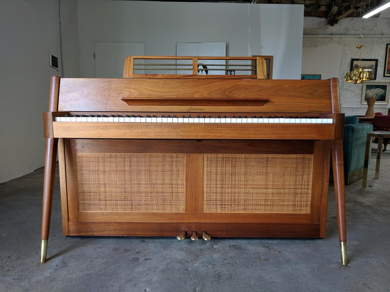 Beautiful grain. Walnut with brass tipped angled legs. Cane on the front and the back. Includes original care instructions and 10 year warranty pamphlet, which has since expired. Sounds great. Has a rare bench. Some of the keys have notes written on