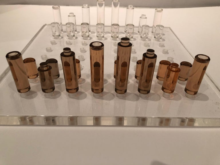Mid-Century Modern Lucite chess set in a unique design. Each chess piece is pegged and fits into holes in the Lucite board. Half are transparent while the opposing pieces are amber in color. Board is .75 thick. Chess pieces are 3 inches, 1.75 and