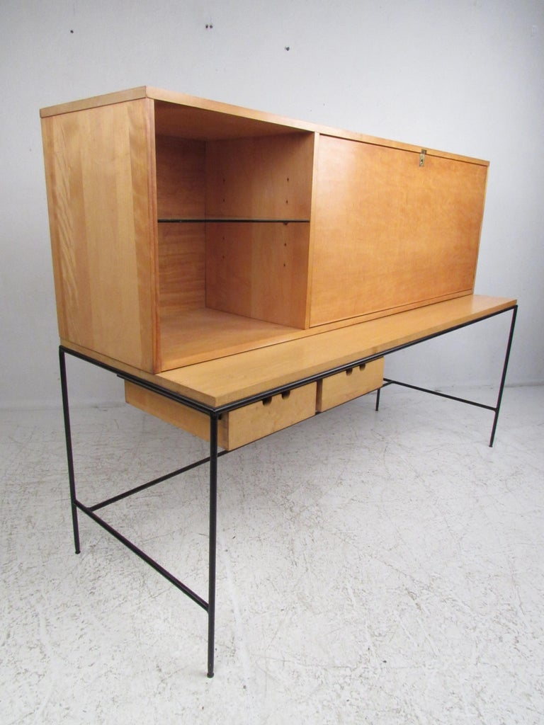 This beautiful vintage modern desk features an enameled steel frame and a maple casing. A stylish design that boasts a large drop front hiding a large compartment and drawers for storage. This rare two-piece desk offers plenty of work space without
