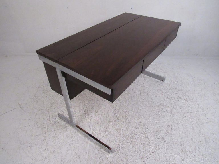 This attractive vintage modern desk features a unique pop-top storage compartment on the top and three large drawers. A one of a kind design with chrome flat bar sled legs and elegant rosewood grain throughout. This well-made case piece has a