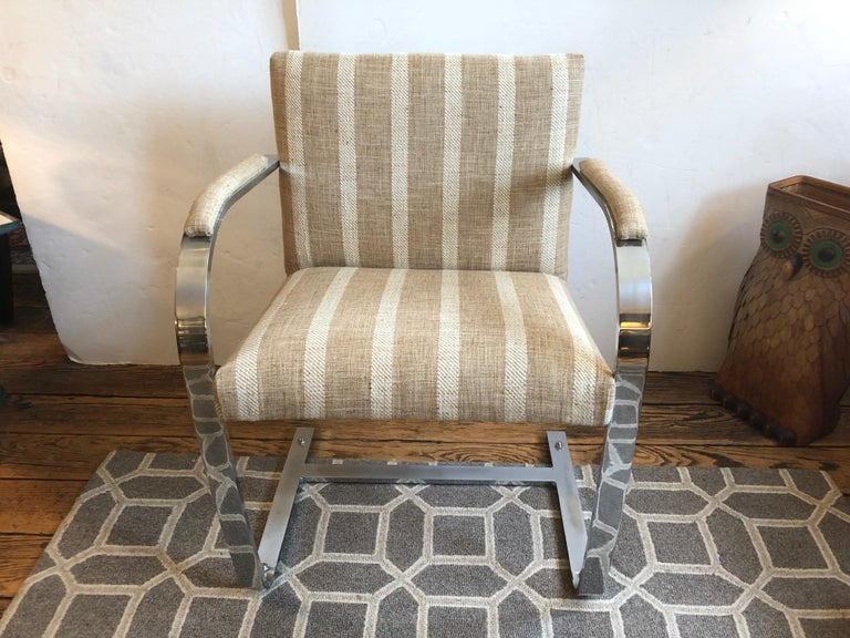 Handsome pair of Mid-Century Modern armchairs in the style of Milo Baughman having heavy chrome curved arms and base, recently upholstered in a neutral chic nubby striped tan and white striped fabric.