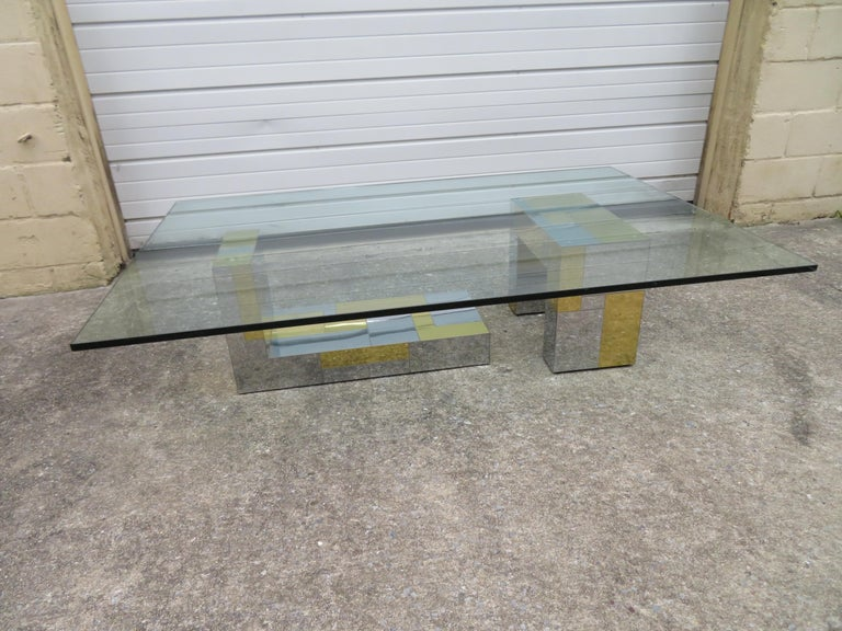 Fabulous Paul Evans for Directional brass and chromed steel coffee table consisting of two sculptural bases supporting an over sized glass top. This particular table is not signed but the original owner did have the original catalog photo from