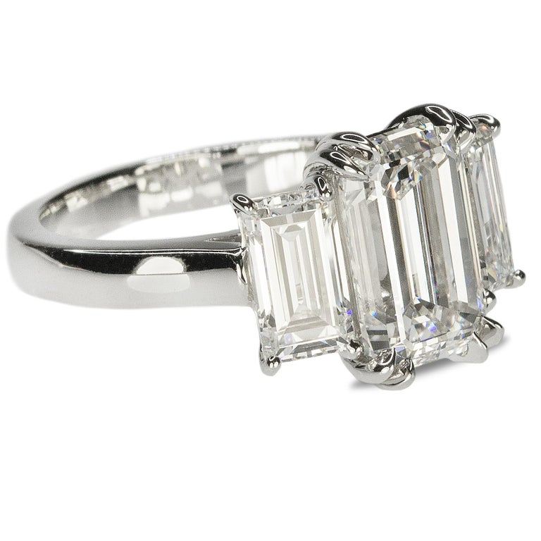 Magnificent hand fabricated platinum three stone ring with one GIA certified 3.02 carat G color VS2 clarity Emerald cut diamond and one 0.83 carat F color VS1 clarity emerald cut diamond on one side and one 0.71 carat E color VS2 laity emerald cut
