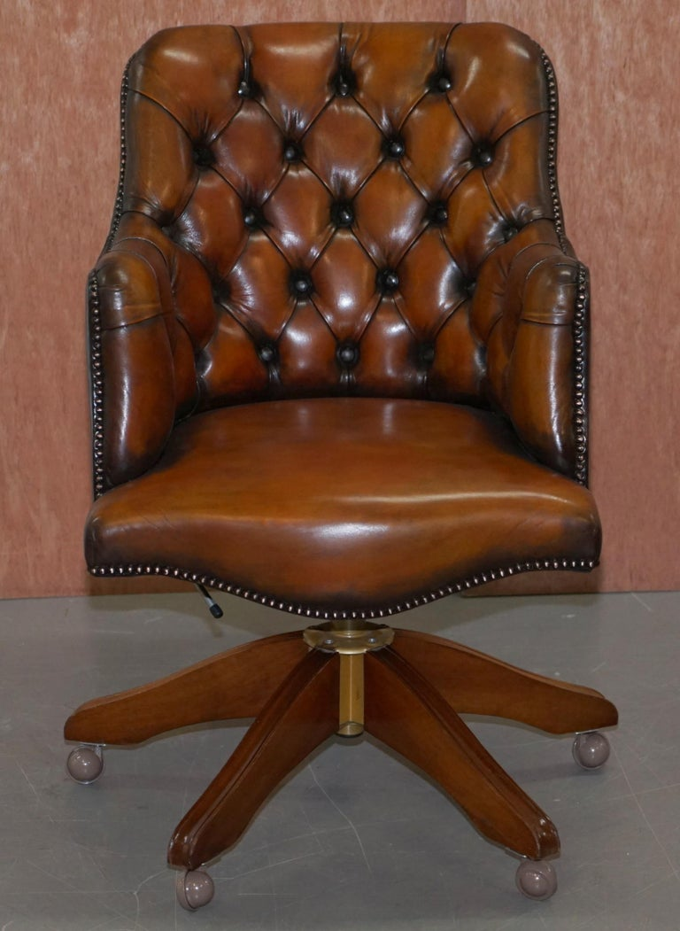 We are delighted to offer for sale this exceptionally comfortable fully restored hand dyed Chesterfield barrel back whisky brown leather directors captains chair  A very good looking and well made piece, originally retailed through Harrods London in