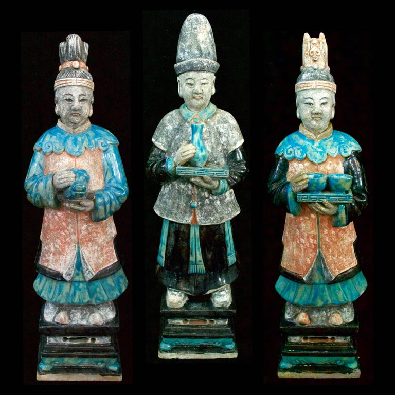 A magnificent trio of Ming Dynasty (1368-1644 CE) court attendants. They wear traditional Daopao Style robes in various blue and red hues. The male attendant being slightly taller at 64 cms, he is wearing a blue robe in an enamel finish, and a black