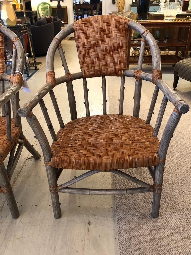 A handsome set of 4 armchairs, great for around a dining table or as living room chairs. The body of the chairs is a grey faux bois with contrasting tan woven rattan seats, back and decorative laces artfully accenting the joints. Measure: Arm