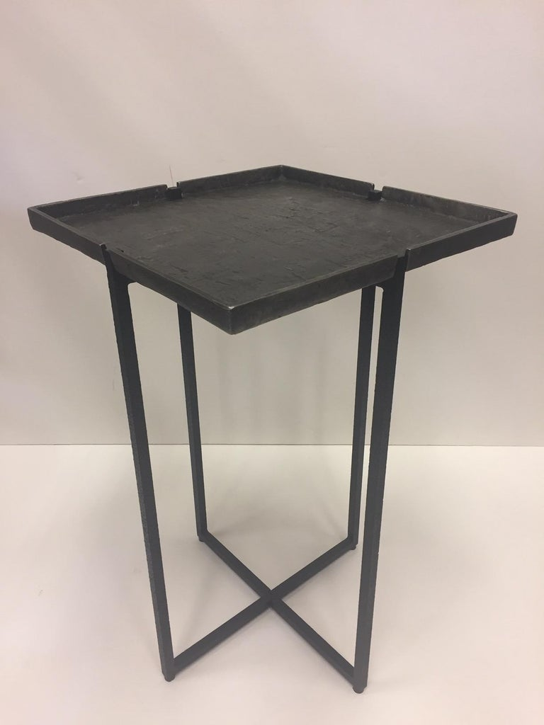 Iron and cast aluminum occasional table having handsome removable square top and elegant criss cross base. Label Michael Aram underneath.