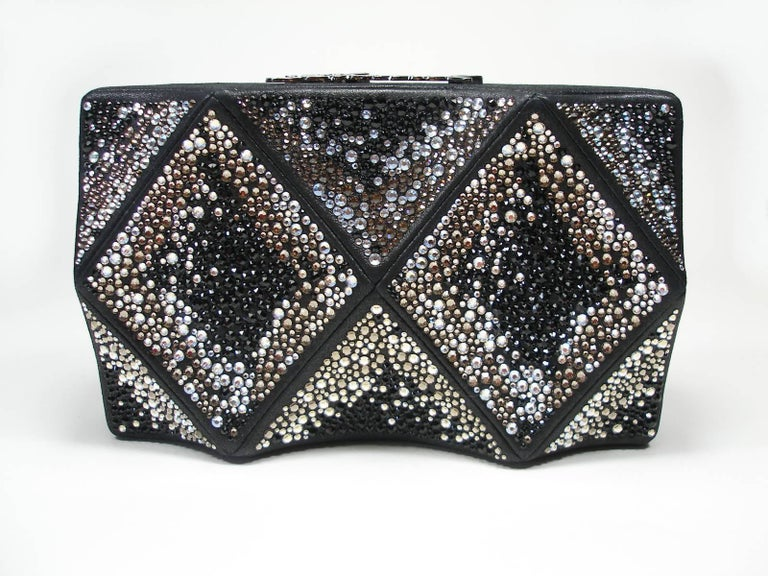 Stunning Minaudière Clutch Chanel  Black leather and crystal de Swarovski Silver / bronze and black Silver color métal Chanel logo on top  Chanel métal plate inside  Made in Italy Size : L 20 X H 12 X 3 P Retail price estimed : $ 6000  Recent
