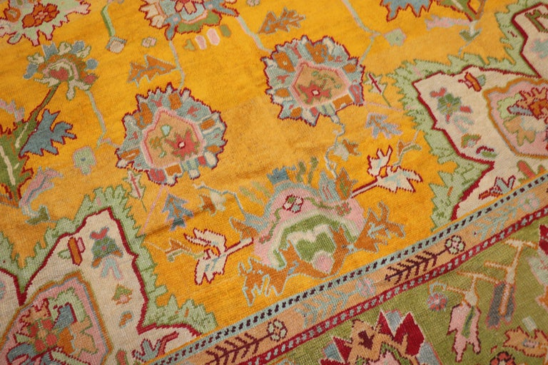 Stunning early 20th century sunshine yellow field antique Turkish Oushak rug. Accents in green, red, golden rod, blue gray, pink simmer throughout 