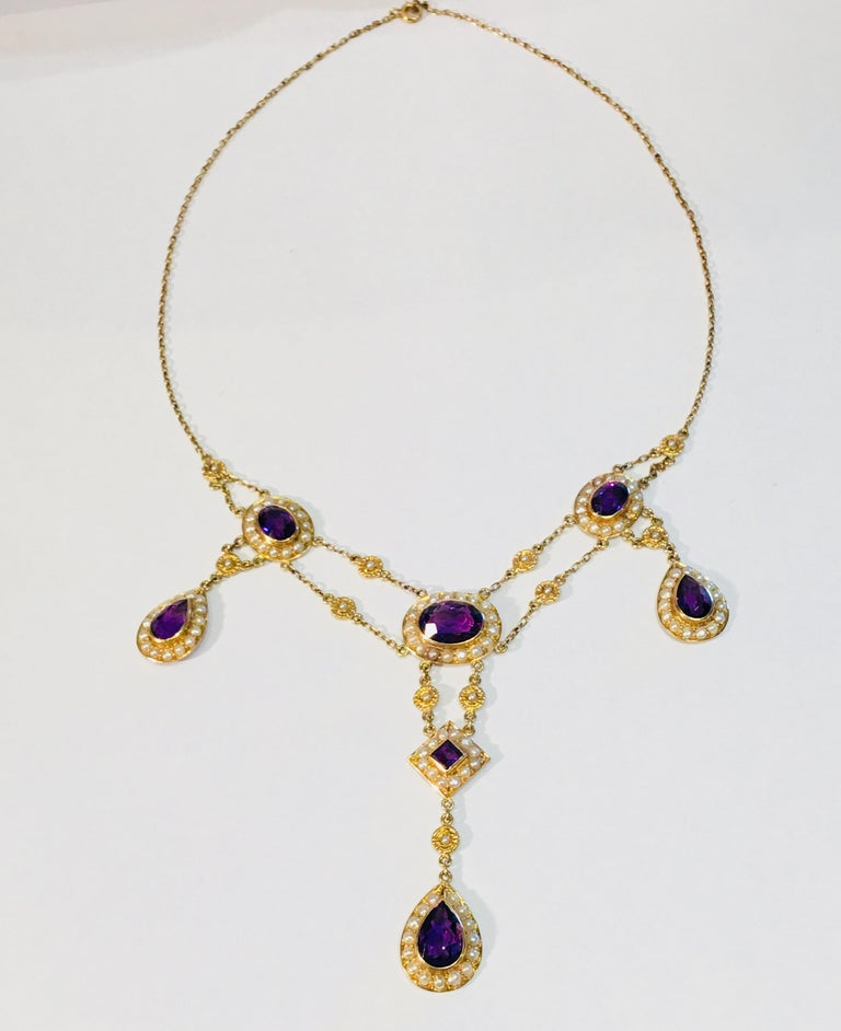 Elaborate, beautifully hand made vintage multi-strand 14 karat yellow gold chain necklace features over 9 carats of the finest quality Siberian amethysts in oval, pear and princess cuts, bezel set and surrounded by halos of seed pearls, and accented