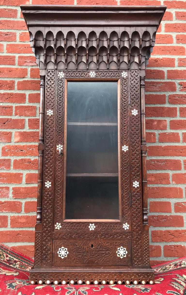 Spanish Colonial Stylish Antique Eastern Style Wooden Wall Hanging Cabinet with Intricate Details For Sale