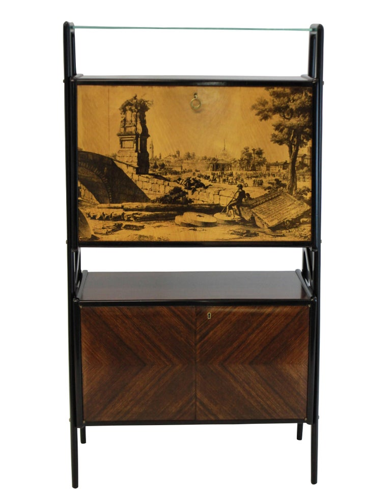 A stunning bar cabinet by Vittorio Dassi in rosewood with a mirrored bar compartment above with a lacquered fall front door depicting a classical scene. A lockable compartment below lined in birch.