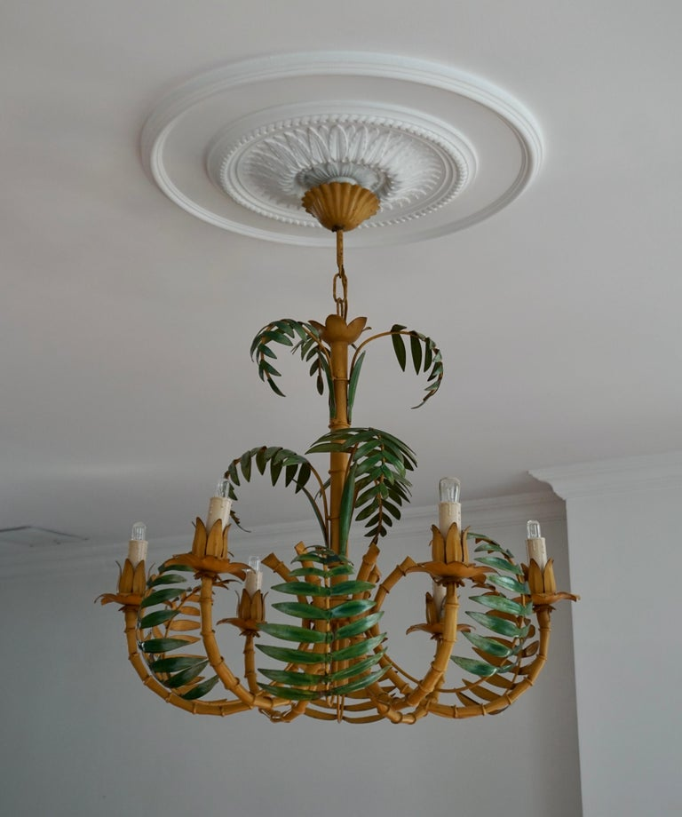 Super chic pale yellow faux bamboo Hollywood Regency chandelier with green leaves, perfect for a hallway or foyer, having 6 arms and wonderful construction of tole, iron and faux bamboo. We love the color. Original canopy and wiring.  Measures: