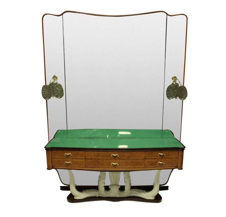 A stylish Italian mid-century hall console with full length mirror with sconces. The console with six drawers in walnut root, with brass handles, a carved faux ivory base and it's original green glass inset top. The mirror is framed in walnut and