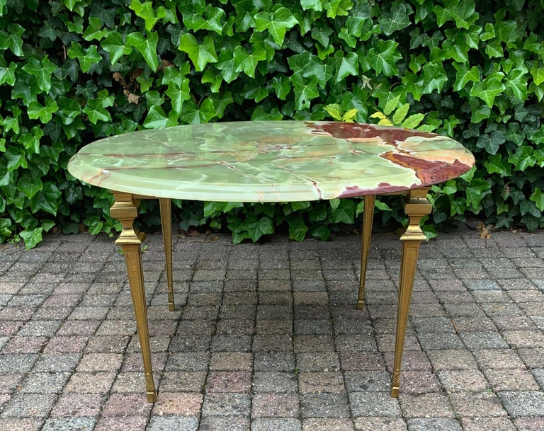 Wonderfully made and great looking table.   This classical design coffee table will look perfect in a classical, in a Hollywood Regency, but also in some contemporary interiors. The slight wear to the bronze base, the overal shape and the wonderful