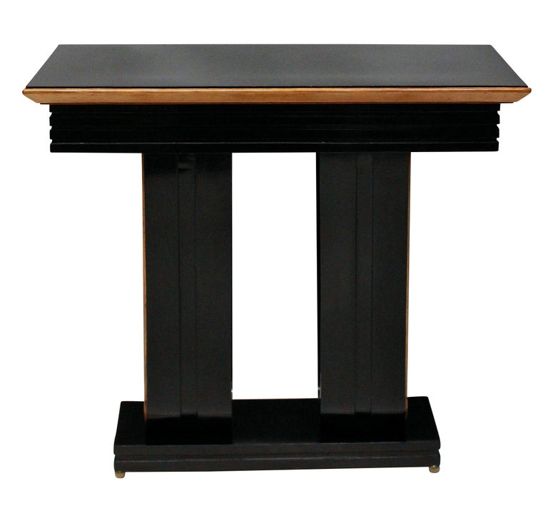 A pair of stylish Italian ebonized console tables with lemon wood detailing and on brass ball feet.
