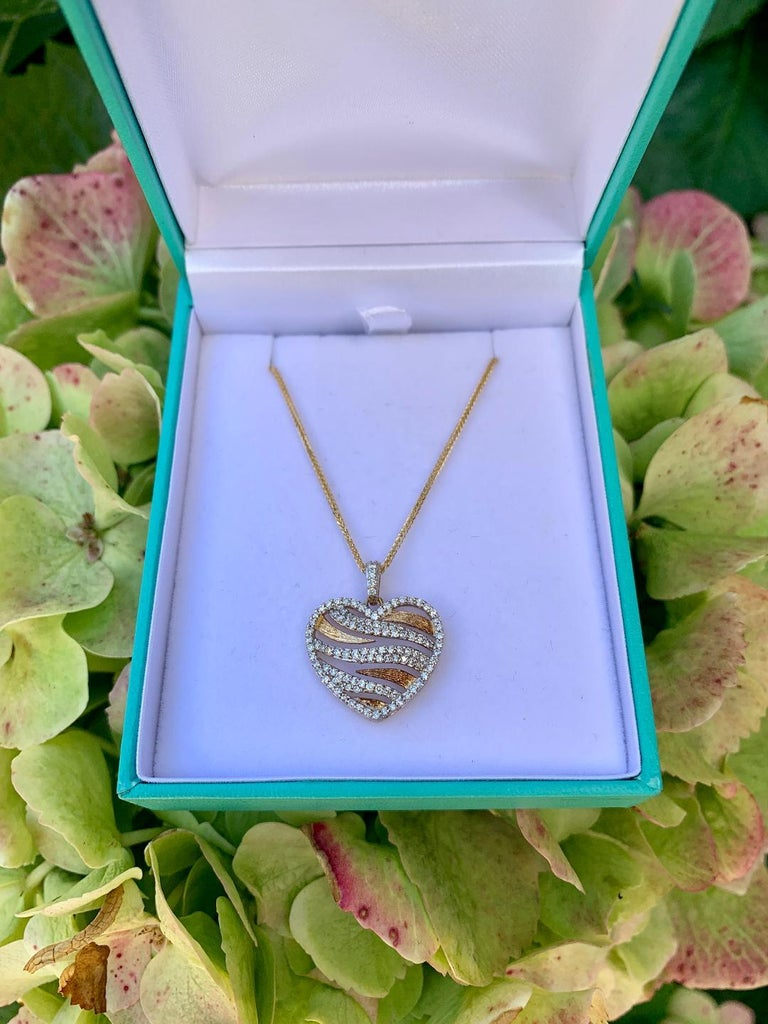 Very stylish, 14 karat yellow gold micro pave diamond heart pendant with diamond bale created in a fun and very fashionable zebra stripe design. Yellow gold stripes are a Florentine finish to create a rich contrast. Pendant features 108 round