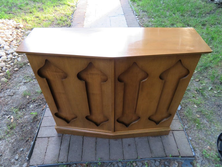 Stylish Harvey Probber style mahogany two-door console cabinet with recessed trefoil design accents. Single stationary shelf interior with a chevron shaped top and cabinet, circa 1970. There is a glass top that was not pictured that is included.