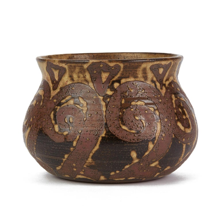 A very stylish and well made vintage studio pottery bowl with a tenmoku glazed swirl design around the body on a light mottled brown ground. The hand thrown bowl is finely made in red terracotta and has an impressed flower mark to the base. Offered
