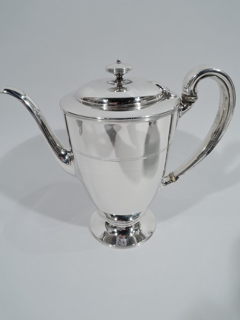 Edwardian Modern sterling silver coffee and tea set. Made by Tiffany & Co. in New York, ca 1907. This set comprises coffeepot, teapot, creamer, sugar, and waste bowl.  Each: Ovoid body with round and raised foot. Handles high looping except waste