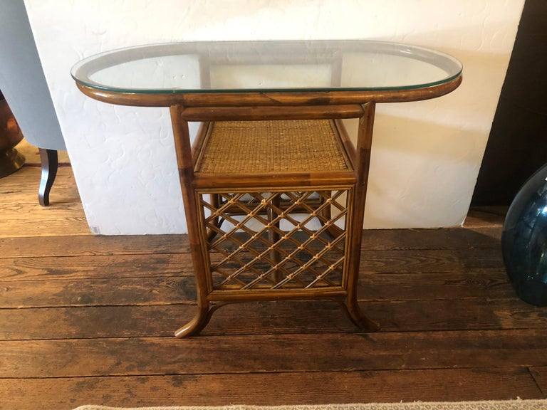A rare and chic 3 piece rattan and bamboo set including two tier oblong console table and matching diminutive curved side chairs. Each has stylishly splayed legs and handsome hatchwork design. The bottom tier of the console is caned, while the top