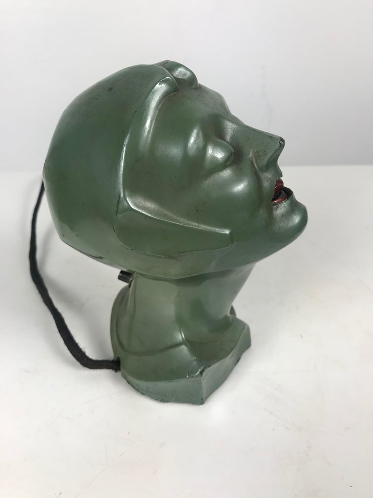 Stylized 1930s Art Deco women's head electric cigarette lighter by Arturo Levi. Retains original paint, finish, as well as original electrical plug and push button that heats up coil in women's mouth. Minor dent and paint loss to back of head,