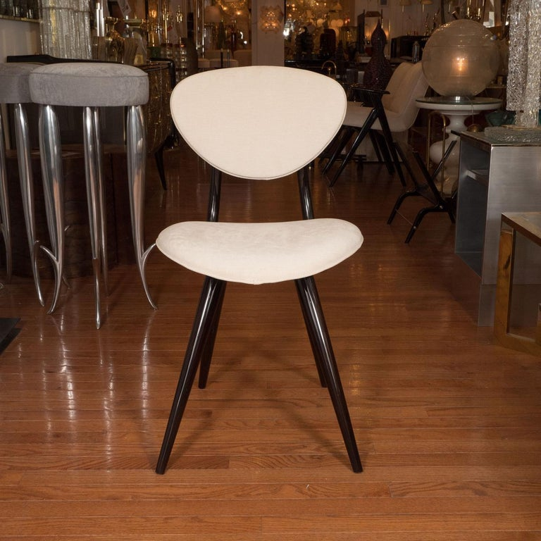 Stylized lacquered wood chairs with ovoid backs and seats by Stella Durera.