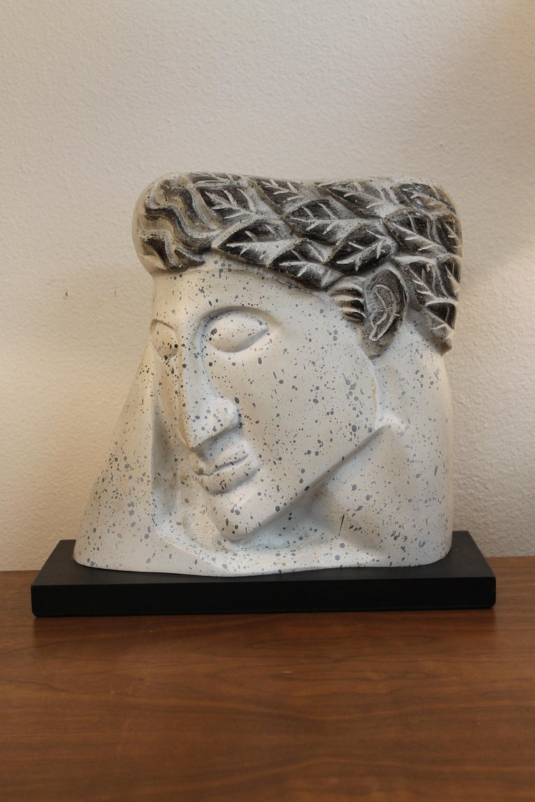 Stylized plaster head on wood stand. Piece isn't signed. Ceramic portion is 13